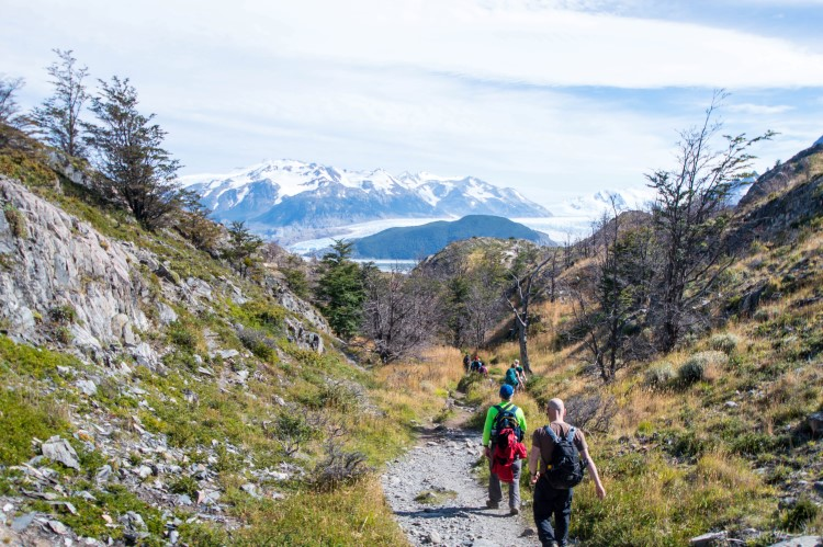 Hikers on the Torres del Paine W trek, Patagonia with views across Glacier Grey