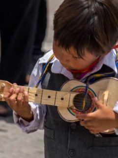 A child playing a small guitar in a carnaval parade in Ayacucho peru