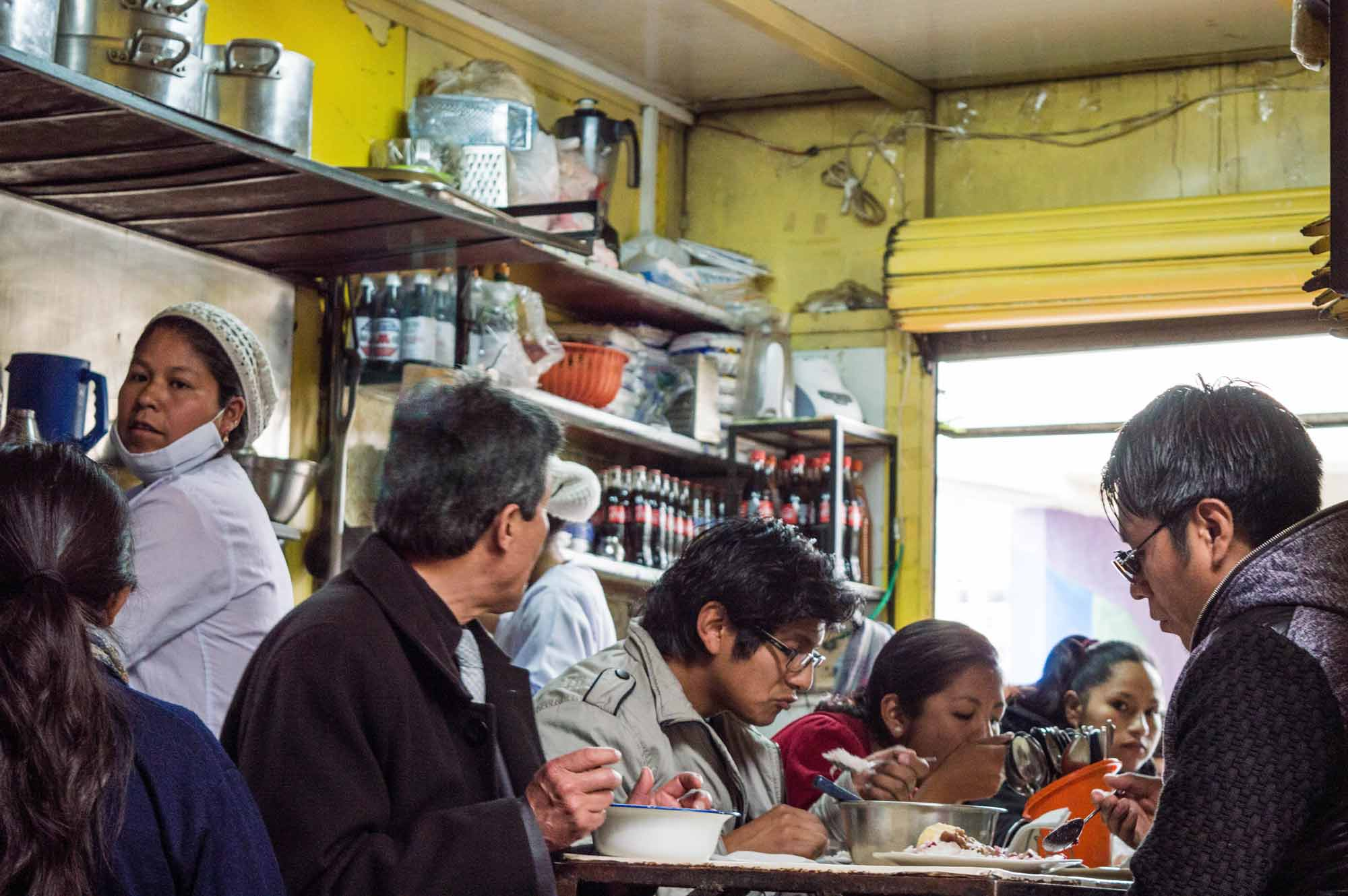 Local diners eating in the Mercado Lanza in La Paz, a great opportunity to meet local people and spend your money in a responsible tourism fashion