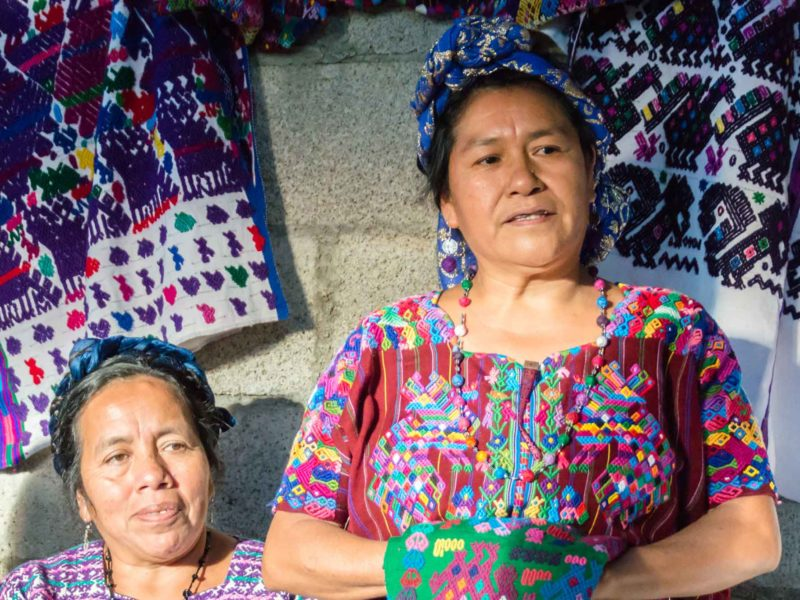 Two women from the Santo Domingo Xenacoj weaving community in Guatemala talk about their textiles to a group of responsible travelers