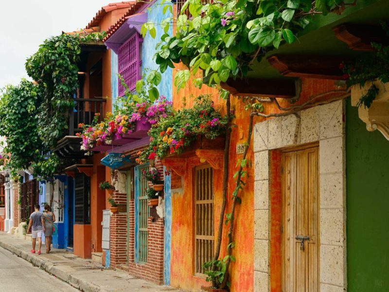 The streets of Colonial Cartagena - brightly painted and covered in flowers. Discover them on these South America Backpacking Routes