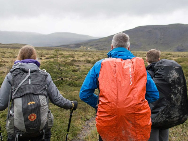Three hikers embarking on the Torres del Paine O Circuit, one of the best hikes in South America