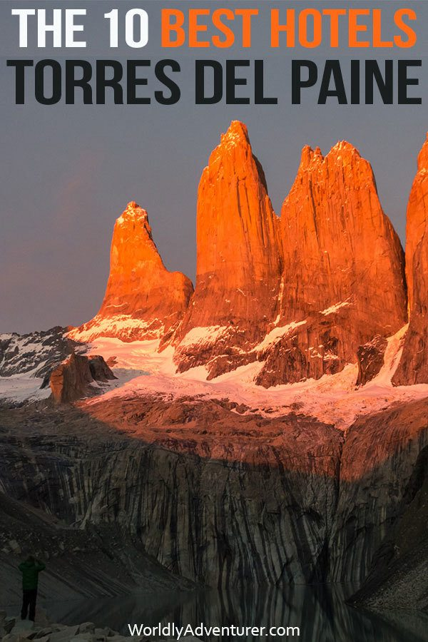 The torres in Torres del Paine National Park at dawn with a hiker standing at their base beside a lake
