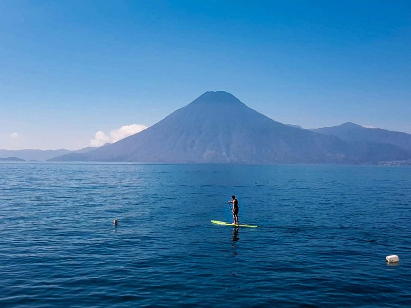 A man paddleboards on the calm waters of Lago Atitlan with a volcanic peak in the background, an activity that you can't miss on a trip to Guatemala