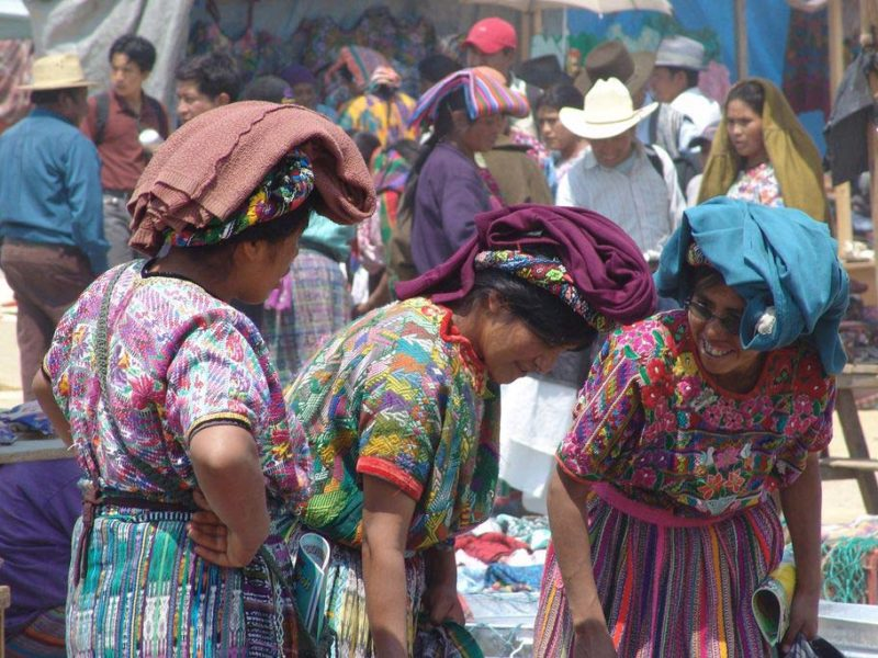 Three women wearing traditional Guatemala huipiles and headpieces converse as they investigate wares at the Mercado San Francisco el Alto, one of the best things to do in Guatemala for tourists