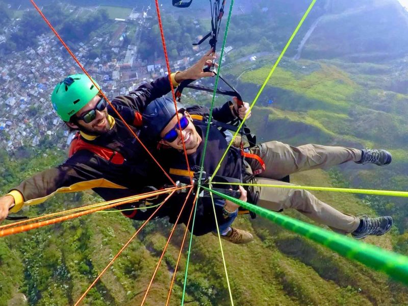 Two men attached to the strings of a paraglide above the hills and a village in Guatemala, one of the most extreme and fun things to do in Gutemala