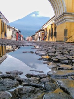 Cobblestones in Antigua Guatemala looking through a colonial archway to a volcano wreathed in morning mist