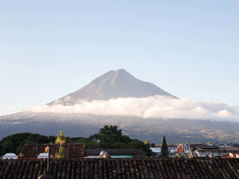 A volcano rises out of the clouds in Antigua Guatemala, a city you can visit can visit on a women travel group tour
