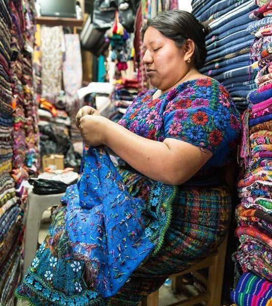 A woman sews at her textile stall in Antigua Guatemala, a city you can visit can visit on a women travel group tour