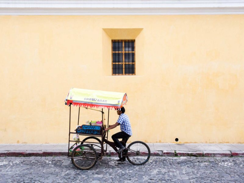A local cycles down a cobbled street in the pretty colonial city of Antigua Guatemala, a city you can visit can visit on a women travel group tour