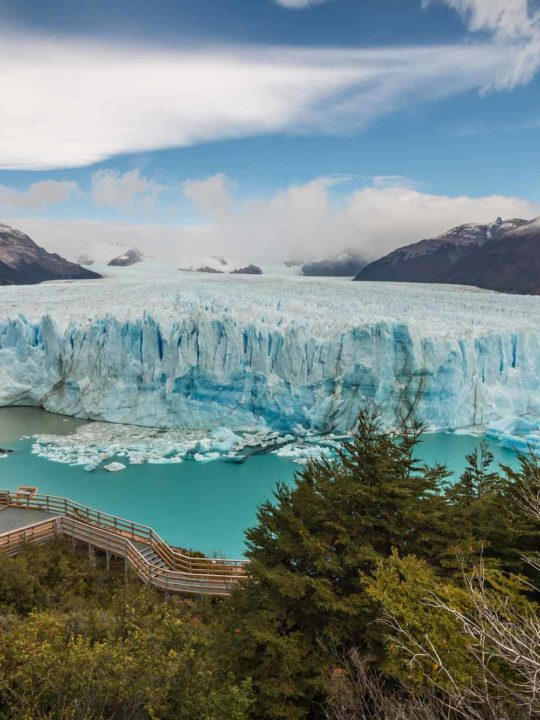 Views of the impressive snout of the Perito Moreno Glacier in Los Glaciares National Park with people stood on boardwalks beneath it.