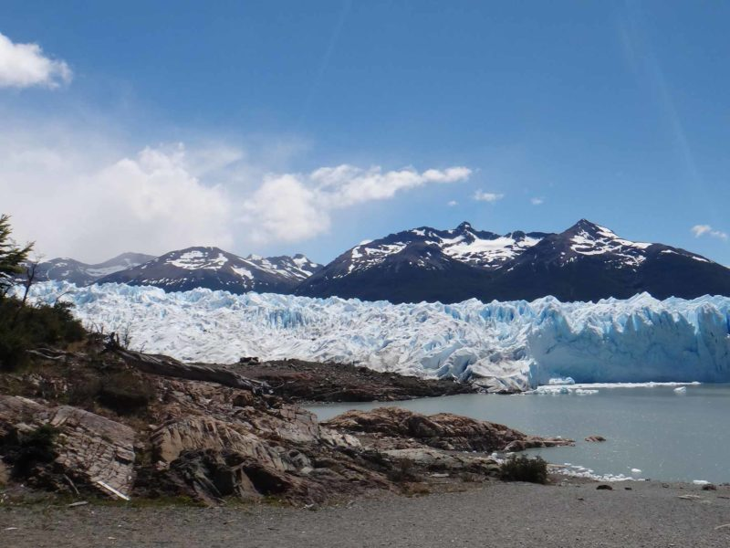 A beach and rocks on Lago Argentina with the wall of the El Perito Moreno Glacier, Argentina in the background