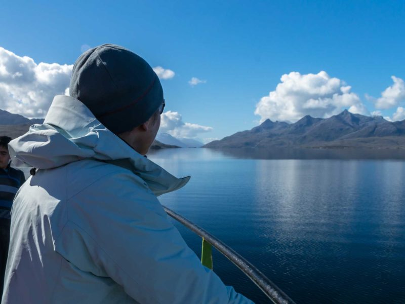 A person stares into the distance at the scenery of the Patagonian fjords aboard a cargo and passenger ferry,one of the ways of getting to Patagonia