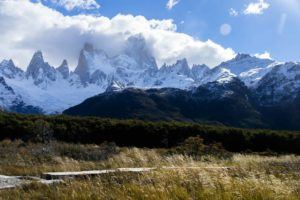 Looking over a forested wilderness to snow covered mountains under a blue sky. Best Hikes in South America.