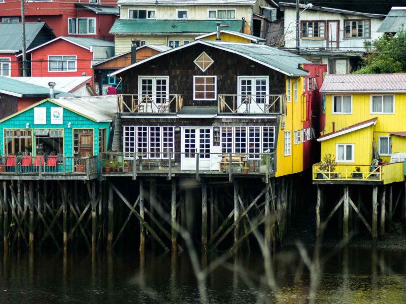 Cheerfully painted palafitos in the island of Chiloe on this South America Backpacking Route.