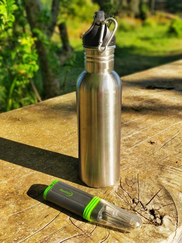 A Steripen Adventurer next to a steel flask on a wooden table, a great gift for adventure travelers
