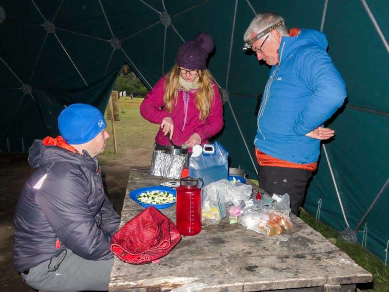 Three hikers in a geodesic dome in Campamento Dickson cook over camping stoves while hiking the O Circuit in Torres del Paine National Park, Patagonia