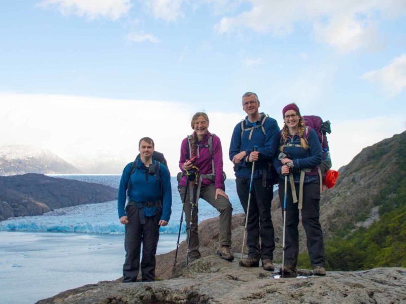 Four hikers in front of Glacier Grey while hiking the O Circuit in Torres del Paine National Park, Patagonia
