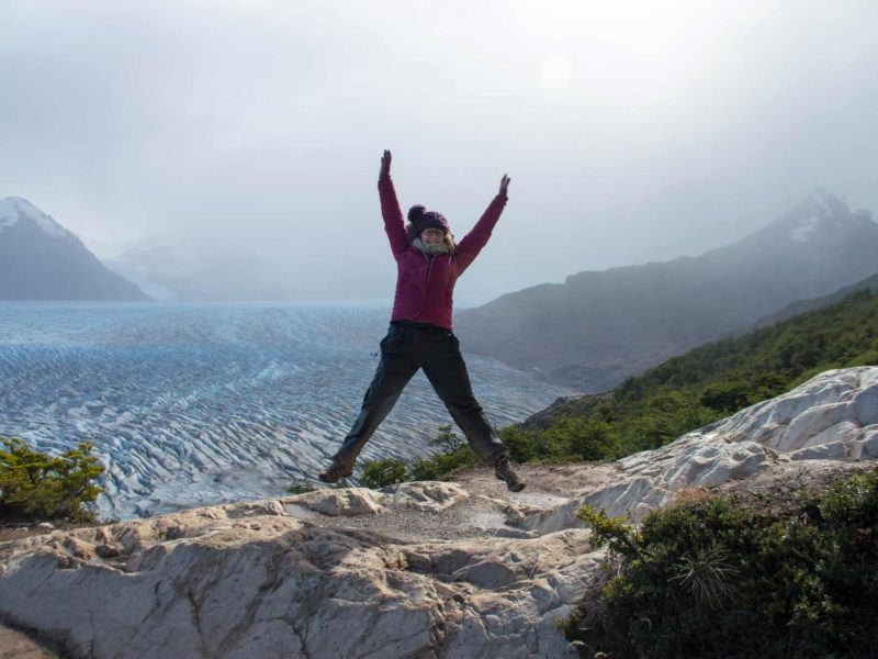 A hiker doing a star jump in front of Glacier Grey while hiking the O Circuit in Torres del Paine National Park, Patagonia