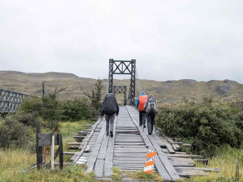 Three hikers cross a bridge while hiking the O Circuit in Torres del Paine National Park, Patagonia