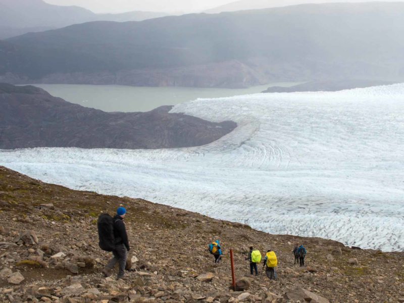 Hikers descending the path from Paso John Gardner with Glacier Grey and the Southern Patagonian Icefield beyond while hiking the O Circuit in Torres del Paine National Park, Patagonia