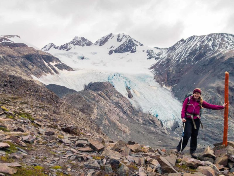 A hiker stands in front of a glacier at the top of Paso John Gardner while hiking the O Circuit in Torres del Paine National Park, Patagonia