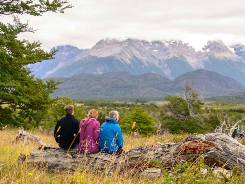 Three people sit on a tree trunk for lunch while hiking the O Circuit in Torres del Paine National Park, Patagonia