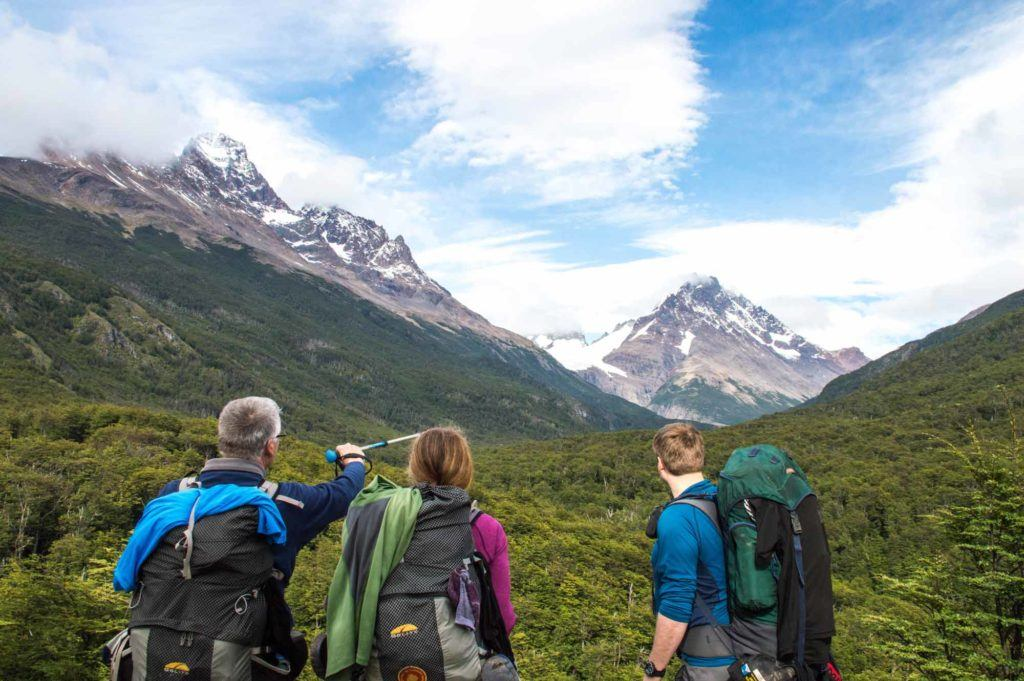 Three hikers look at the path out of Campamento Dickson while hiking the O Circuit in Torres del Paine National Park, Patagonia