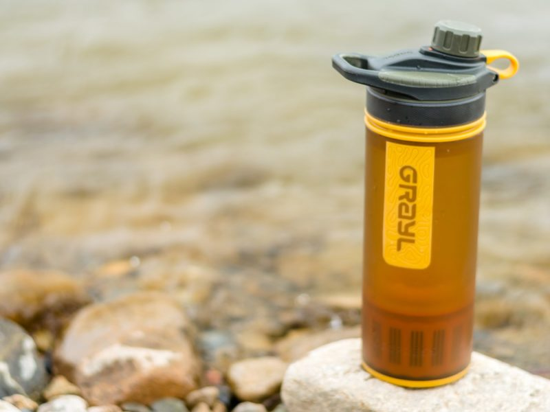 An orange Grayl Geopress travel water filter sits on a rock in front of a river