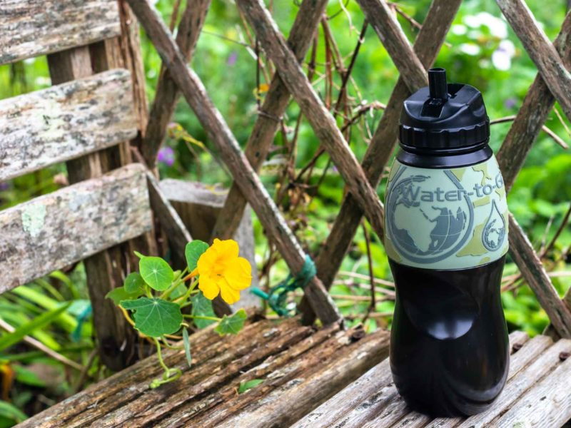 A black and green Water-to-Go water bottle sits on a rustic wooden bench amid yellow flowers