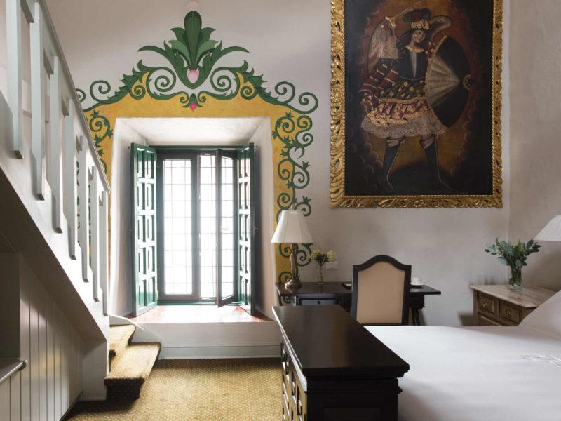 A simply furnished Cuzco hotel room with elaborate painted decoration around the window