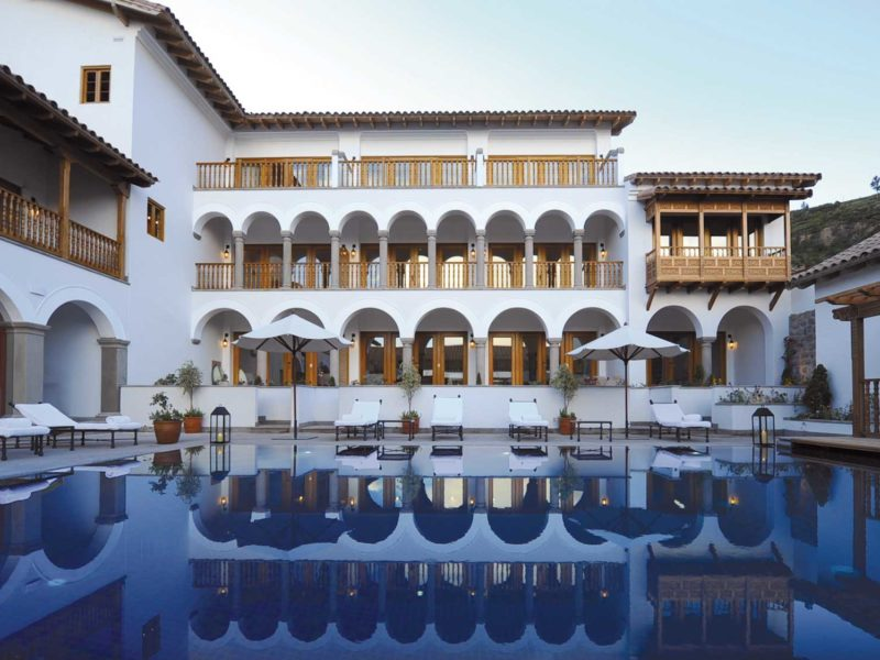 A white hotel with many arched balconies over looks a dark blue swimming pool in Cuzco