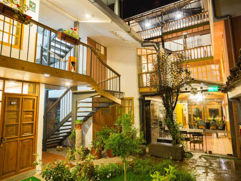 A patio garden is surrounded by the brightly lit hallways and balconies of the Cuzco MOAF boutique hotel