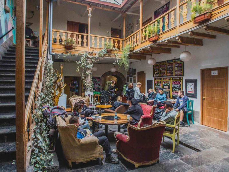 A dozen backpackers chat around a table in the hostel courtyard, they're surrounded by stairs and a wooden balcony.