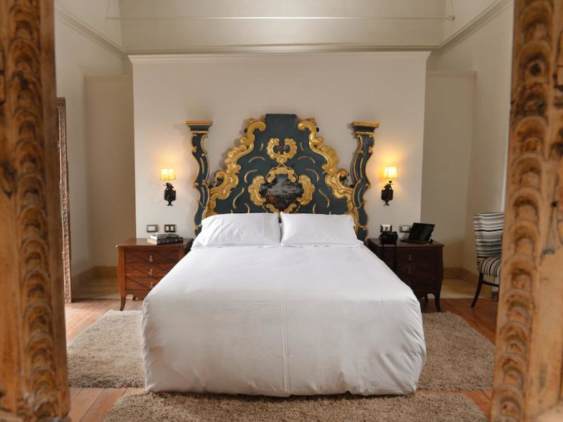 An elaborately carved and painted bed is the centerpiece of the otherwise simply decorated room in this boutique hotel