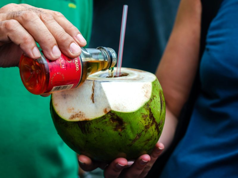 In Guyana a man adds rum to a coconut to create a popular local drink.
