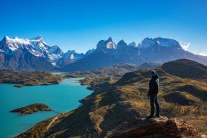 A man stands at Mirador Condor on a day hike in Torres del Paine, looking across Lago Pehoe and the mountains of the Cordillera Paine beyond