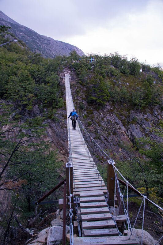 A hiker stands on a wooden hanging bridge on a day hike in Torres del Paine National Park