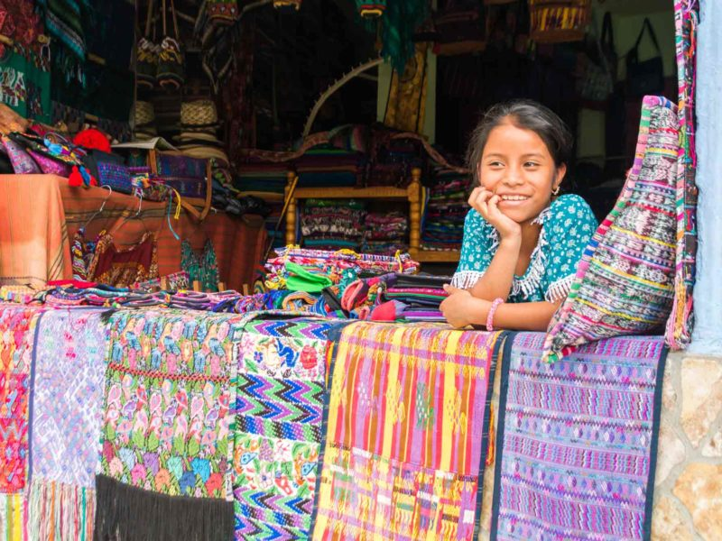 A girl leans over textiles at a stall in Panajachel, a village on the shores of Lago de Atitlan, a must-visit destination on any Guatemala itinerary