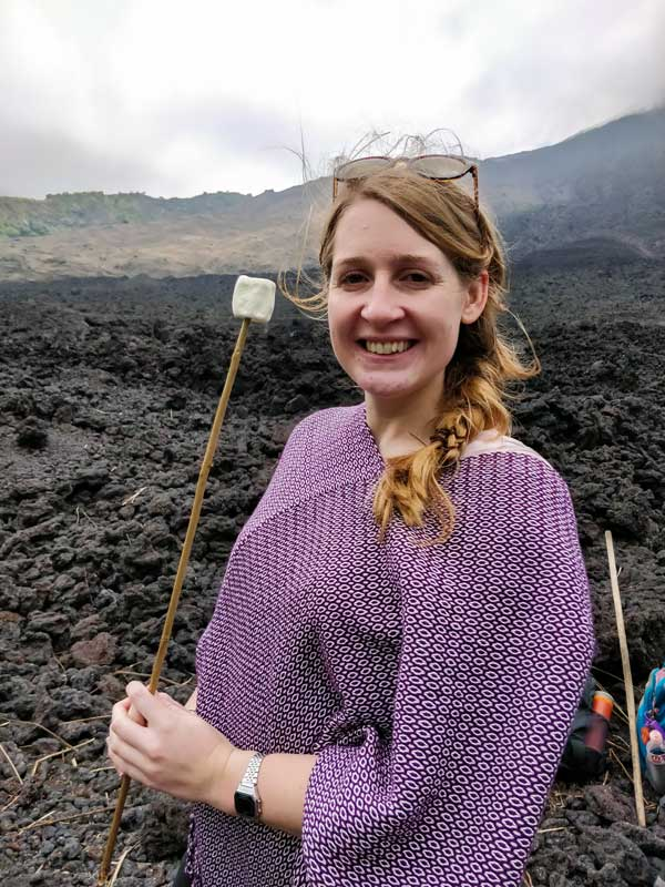 Worldly Adventurer stands with a marshmallow on Volcan Pacaya, a must-visit destination on a Guatemala itinerary