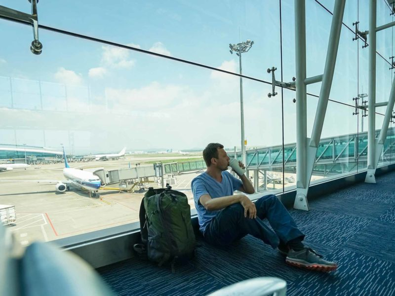 A traveller sits on the floor in an airport while drinking from a coffee cup