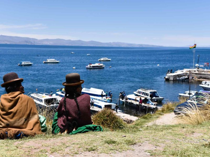 Two cholitas in traditional Andean dress sit on a hill overlooking Lake Titicaca on Isla del Sol