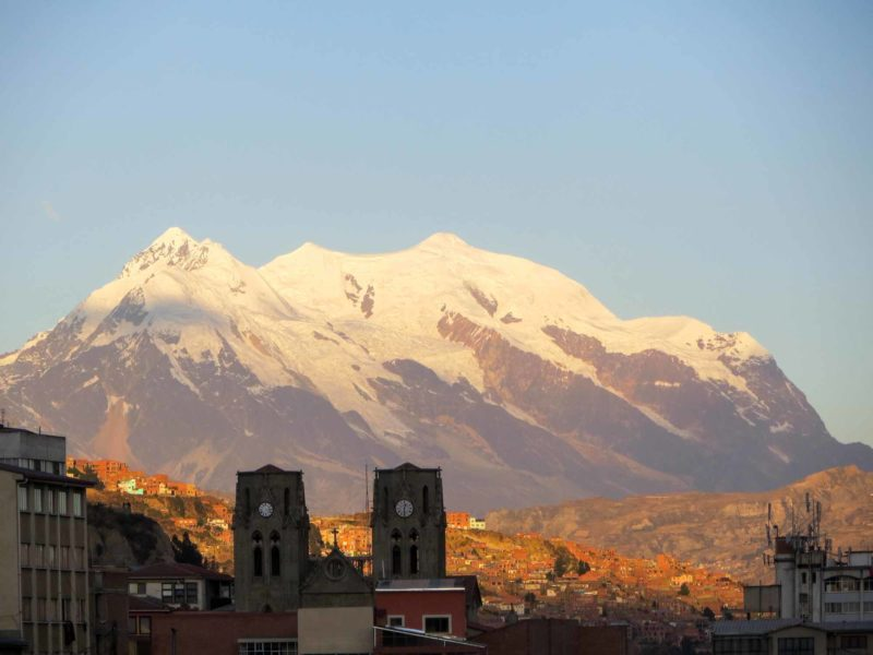 The snow-dusted peaks of Illimani are lit up in the sunrise above La Paz in Bolivia