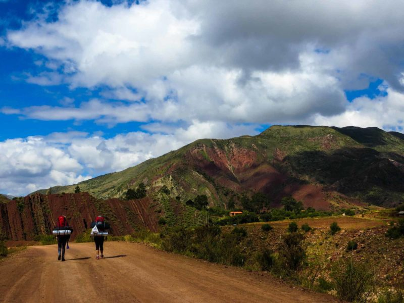 Two hikers walking along a path next to rainbow coloured rock in the Maragua Crater near Sucre, Bolivia