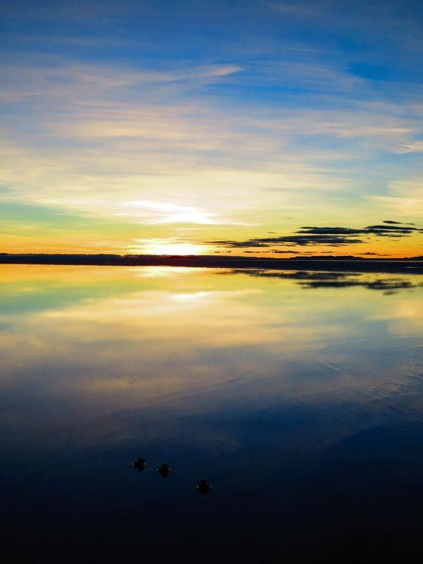 The Salar de Uyuni in Bolivia with water on top reflecting the sunrise like a mirror